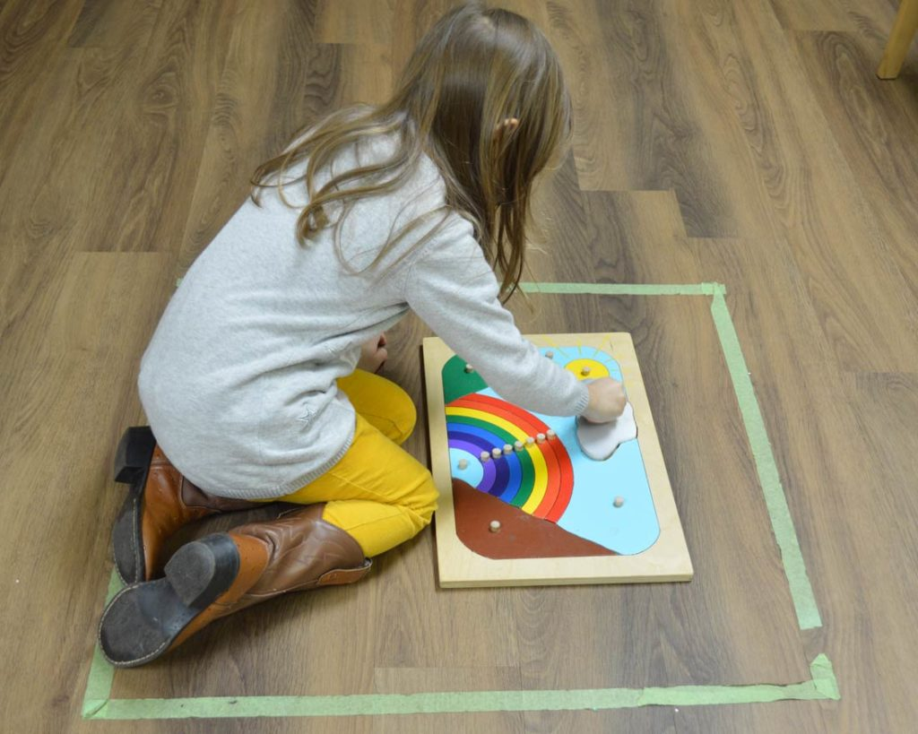 A child sitting in a taped off box on the floor and working on a rainbow puzzle.