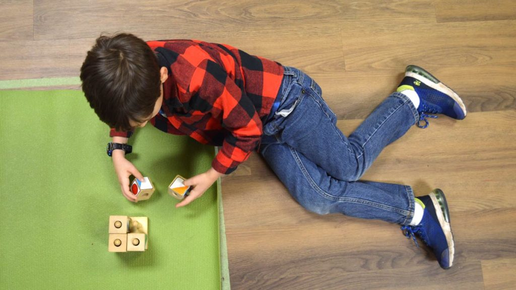 A little boy playing with blocks on a green mat