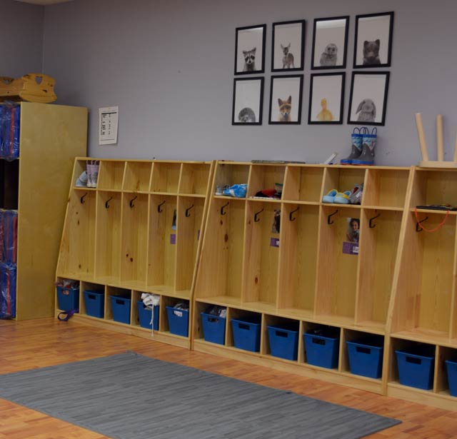 A series of cubbies and blue bins in a classroom.