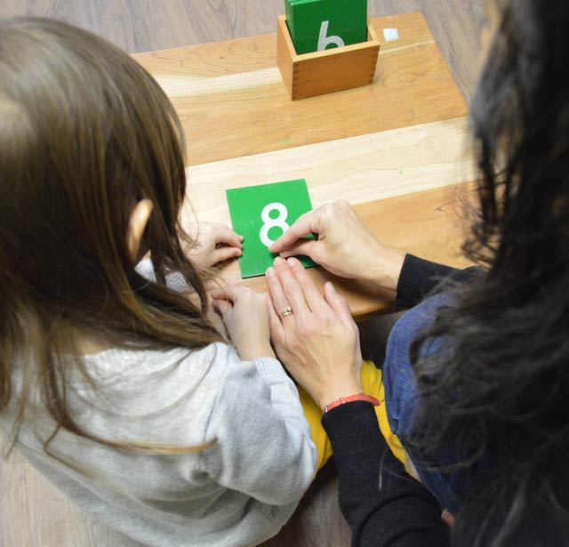 A teacher and a student holding green counting cards with #8 on the card